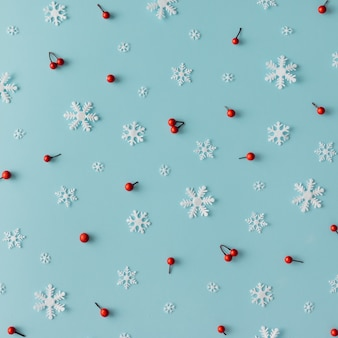 Padrão de natal feito de flocos de neve e bagas vermelhas na parede azul. conceito de inverno. postura plana.