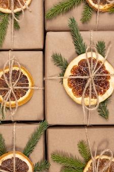 Padrão de natal ou ano novo de caixas em papel artesanal com laranjas secas, ramos de abeto e close-up de barbante.