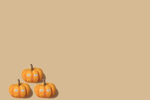 Padrão de outono na cor amarela e laranja. fundo mínimo de mini abóboras de halloween. layout criativo. cara de abóbora sorridente feliz.
