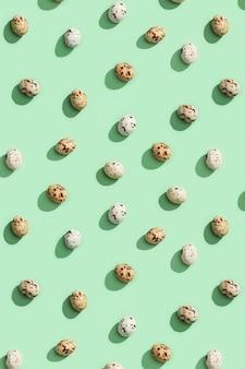 Padrão de páscoa de ovos de codorna de cor bege. flat lay primavera páscoa com bombons de chocolate.