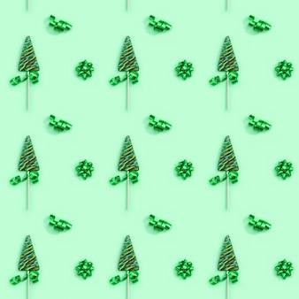 Padrão de pirulitos em forma de árvore de natal na superfície verde