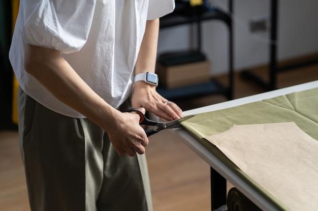 Padrão de tecido de corte sob medida para vestuário feminino esgoto mão segure material de tesoura na mesa em estúdio