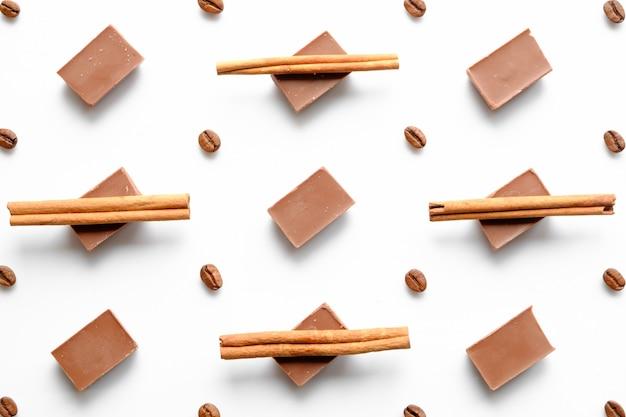 Padrão de tijolos de chocolate como fundo com grãos de café e canela na vista superior branca
