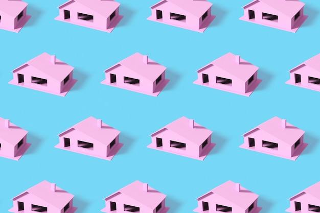 Padrão de verão criativo feito com casas cor de rosa sobre fundo azul.