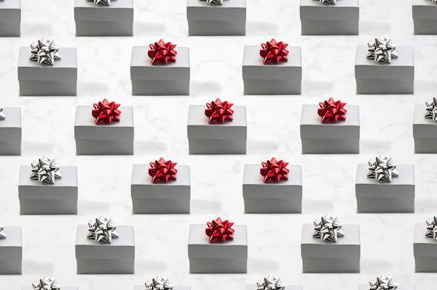 Padrão em forma de coração feito de caixas de presente de prata com fita vermelha e prata em mármore vista frontal plano
