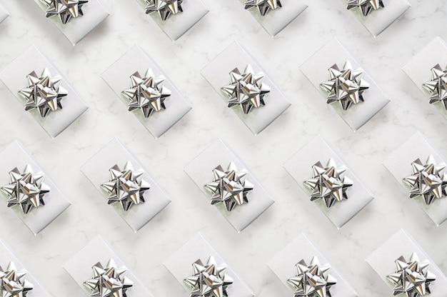 Padrão feito de caixas de presente de prata com fita de prata em mármore estilo isométrico padrão monocromático vista de cima plana