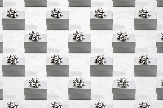 Padrão feito de caixas de presente de prata com fita de prata na vista frontal de mármore padrão monocromático plano