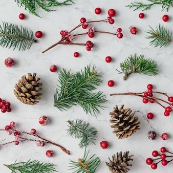 Padrão feito de galhos de árvores de natal, pinhas e bagas vermelhas na parede de mármore. conceito de natal. postura plana.