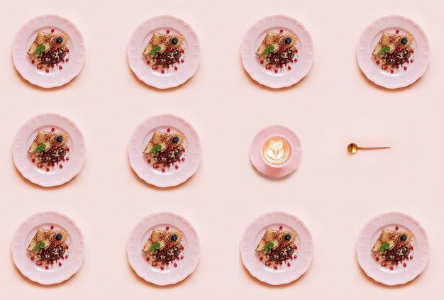 Padrão geométrico com panquecas no prato rosa e xícara de café no fundo rosa.