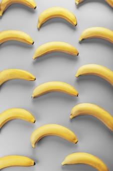 Padrão geométrico de bananas amarelas em um fundo cinza