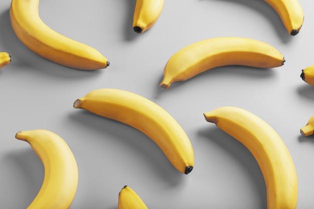 Padrão geométrico de bananas amarelas sobre um fundo cinza nas cores da moda de 2021.