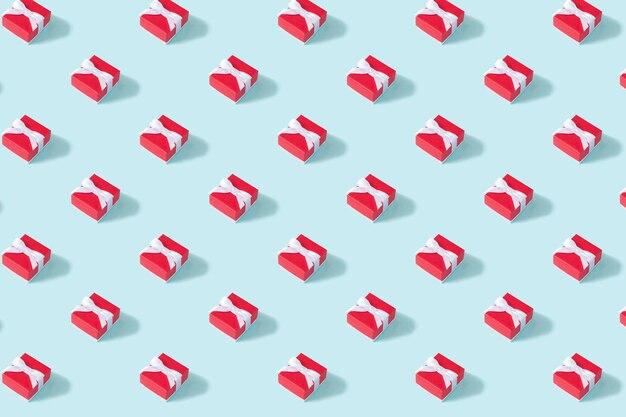 Padrão isométrico de natal criativo feito de caixa de presente vermelha sobre fundo azul. conceito mínimo de natal ou ano novo.