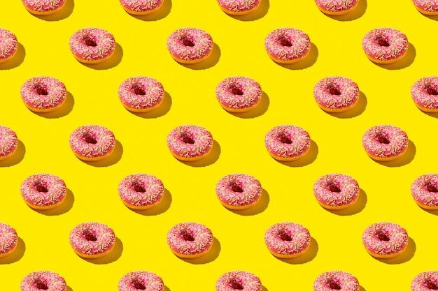 Padrão liso leigo de saborosa rosquinha rosa sobre fundo amarelo.