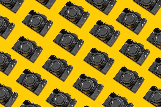Padrão moderno de câmeras retrô em um fundo amarelo. fundo horizontal foto conceito