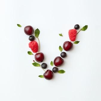 Padrão orgânico de bagas do alfabeto inglês da letra v a partir de frutas maduras naturais - groselha preta