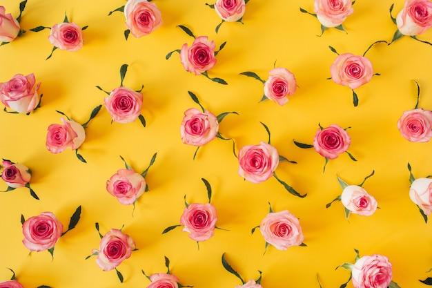 Padrão plano de folhas e botões de flores de rosa rosa em amarelo
