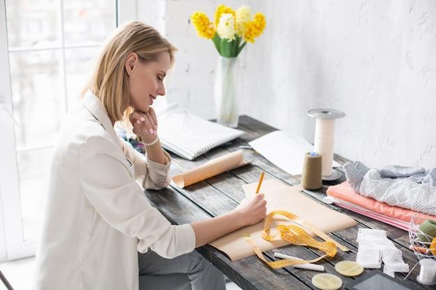 Padrão preciso. artista atraente e reflexiva tocando o rosto enquanto trabalha no padrão