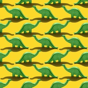Padrão sem emenda com dinossauro diplodocus verde em fundo amarelo