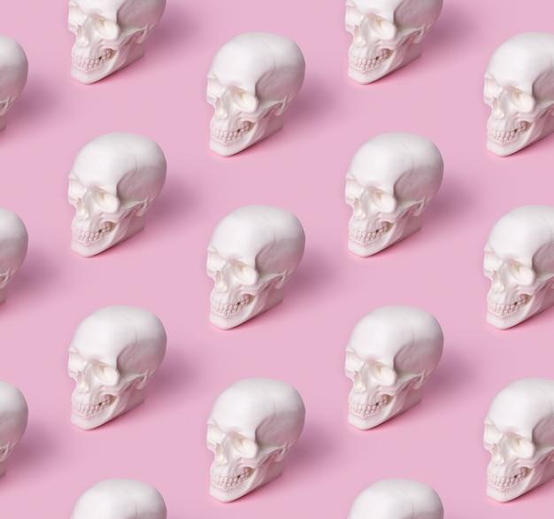 Padrão sem emenda de caveira na mesa rosa pastel.