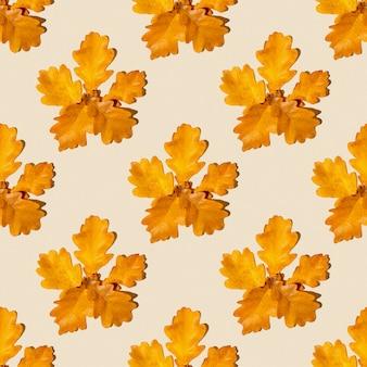 Padrão sem emenda de folhas secas de outono em um fundo laranja claro