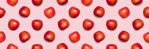 Padrão sem emenda de maçãs em um fundo rosa.
