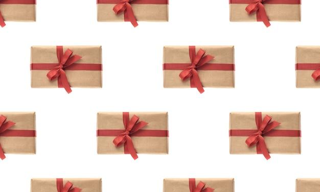Padrão sem emenda de natal. giftbox embrulhado em papel artesanal com fita vermelha isolada no fundo branco. conceito de celebração de natal, inverno, ano novo. camada plana, vista superior, espaço de cópia