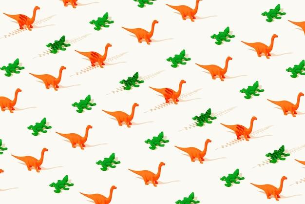 Padrão sem emenda de papel de parede criativo de dinossauros laranja de borracha e crocodilos verdes sobre um fundo amarelo claro.