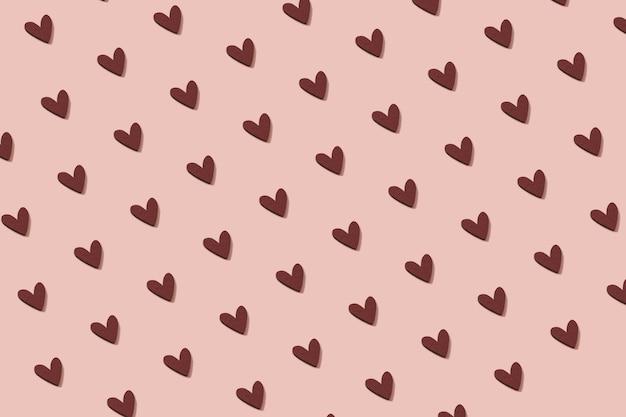 Padrão sem emenda feito de ornamento de coração de madeira em um fundo rosa pastel.
