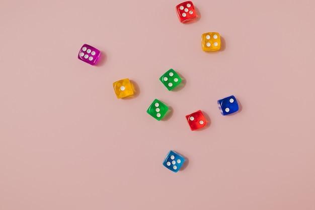 Padrão sem emenda moderno feito com diferentes cores vibrantes joga dados em um fundo rosa pastel. chance de sorte e cenário de jogo de azar.