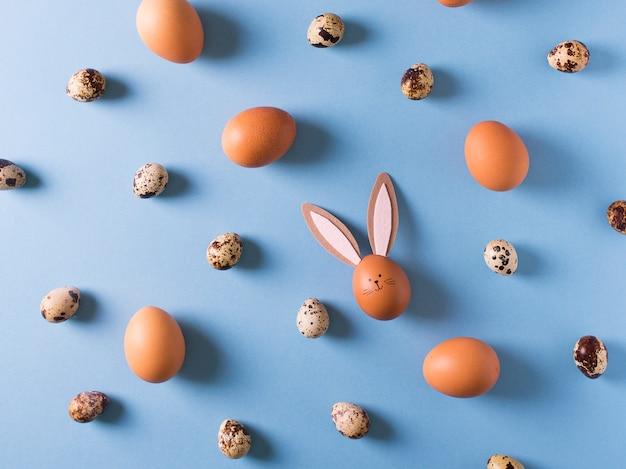 Padrão, textura de ovos de páscoa com coelho em fundo azul