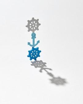 Padrão vertical de rodas de plástico de símbolos marinhos e âncora com sombras longas duras em sombras cinza claras, copie o espaço.