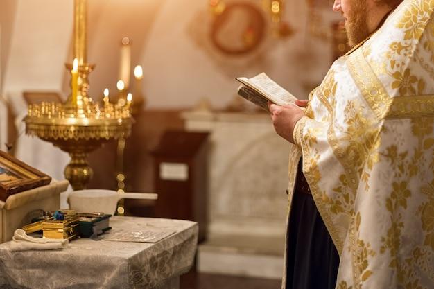 Padre vestindo manto de ouro na cerimônia na igreja catedral cristã, evento sacramental sagrado.