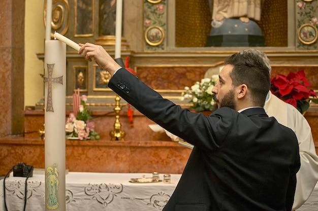 Padrinho no batismo segura e acende a vela, símbolo de uma parte da cerimônia cristã