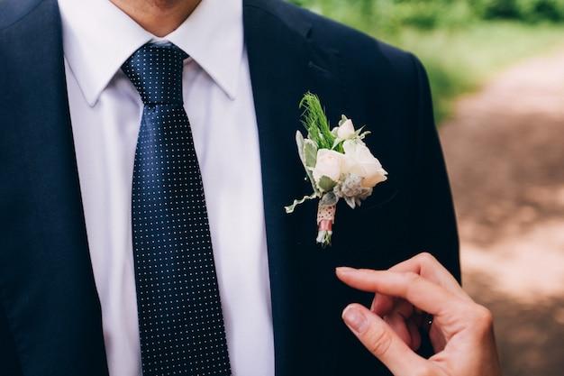 Padrinhos elegantes, ajudando o noivo feliz se preparando a manhã para a cerimônia de casamento. homem de luxo no terno no quarto. dia do casamento.