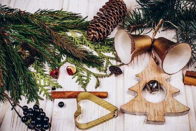 Padrões de madeira para biscoitos, sinos e ramos de abeto na mesa