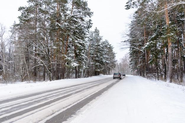 Padrões na rodovia de inverno na forma de quatro linhas retas. estrada nevada no fundo da floresta coberta de neve. paisagem de inverno.