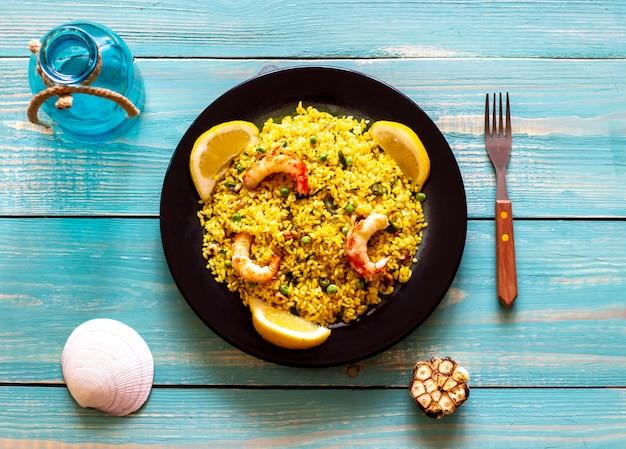 Paella com camarão em um fundo azul de madeira