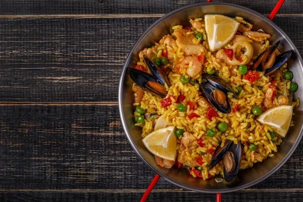Paella com frango, frutos do mar, legumes e açafrão servidos na panela tradicional.