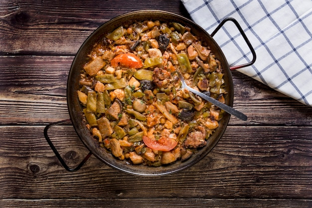 Paella com legumes na mesa de madeira, refeição tradicional, colher, refeição familiar