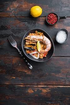 Paella de especialidades de frutos do mar em uma tigela na velha mesa de madeira escura, vista superior com espaço para texto, foto de comida.