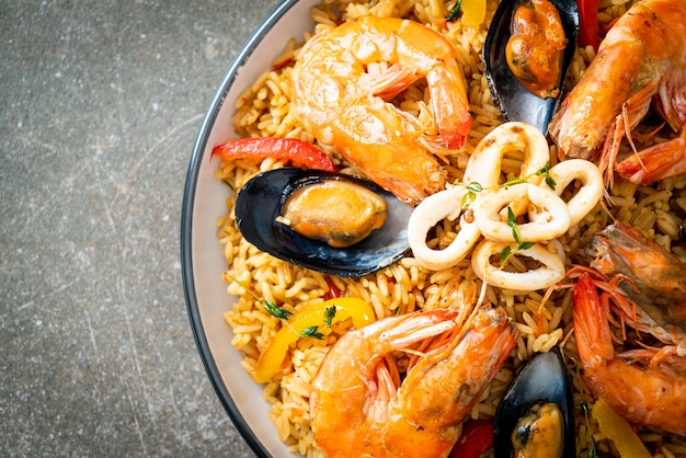 Paella de frutos do mar com camarões, amêijoas, mexilhões com arroz de açafrão - comida espanhola