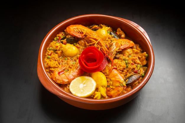 Paella de frutos do mar em uma tigela de cerâmica em madeira escura. arroz com frutos do mar.