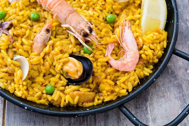 Paella de frutos do mar espanhol tradicional na mesa de madeira