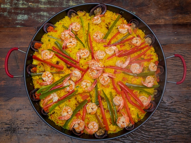 Paella de frutos do mar tradicional na frigideira em uma mesa de madeira velha.