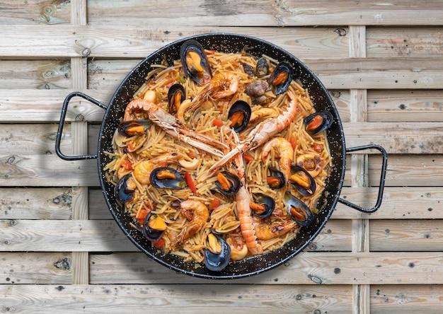Paella de massa de frutos do mar, culinária espanhola em mesa de madeira, vista de cima