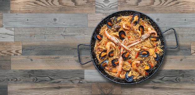 Paella de massa de frutos do mar, culinária espanhola isolada em fundo de madeira, espaço de cópia