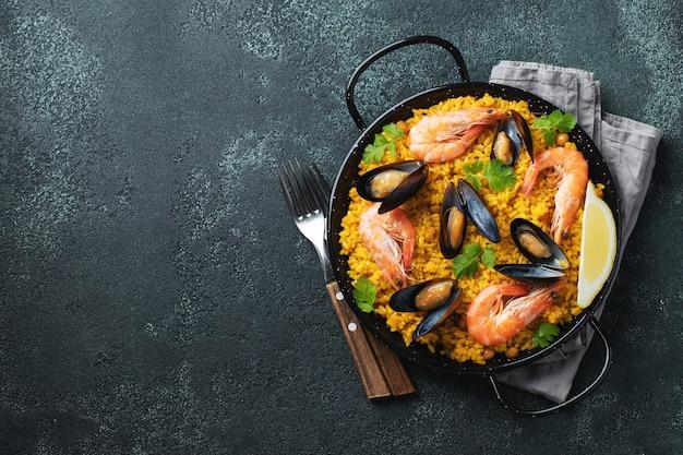 Paella espanhola tradicional de frutos do mar na panela com grão de bico, camarão, mexilhão, lula. vista do topo.