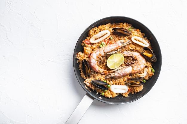 Paella espanhola tradicional de frutos do mar na panela sobre fundo branco, vista superior com espaço para texto, foto de comida.