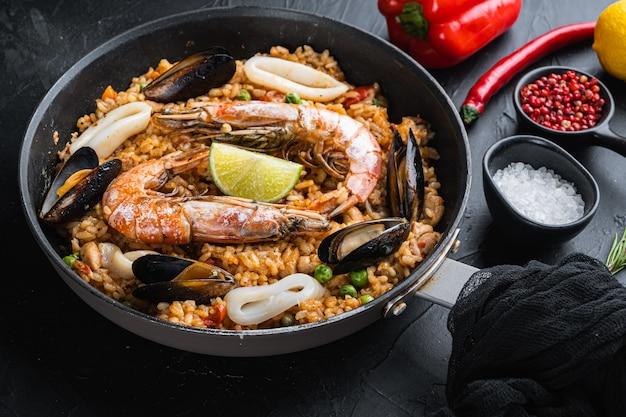 Paella prato tradicional espanhol servido na frigideira, em superfície texturizada preta