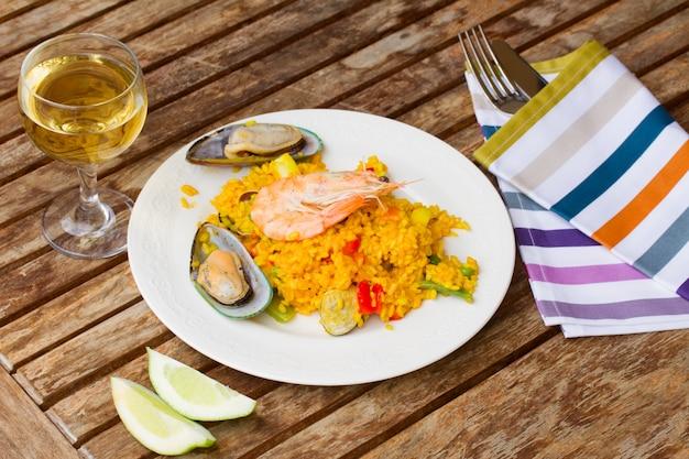 Paella, servido no prato na mesa de madeira